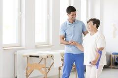 Rörelsehindrad hög kvinna under rehabilitering arkivbilder
