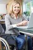 Rörelsehindrad kvinna i rullstol genom att använda bärbara datorn hemma arkivbild
