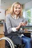 Rörelsehindrad kvinna i rullstolen som hemma smsar på mobiltelefonen royaltyfria foton