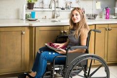 Rörelsehindrad kvinna som gör hussysslor arkivbild