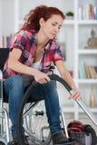 Rörelsehindrad kvinna som hemma använder dammsugare arkivfoto
