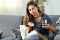 Rörelsehindrad kvinna som ser många preventivpillerar arkivbilder