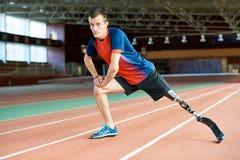 Rörelsehindrad löpare som sträcker i stadion arkivbilder