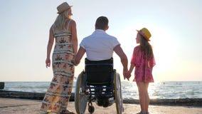 Rörelsehindrad man för gravid flickauppehällearm i rullstol stock video