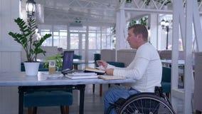 Rörelsehindrad man i hjulstol som talar genom att använda appen på bärbar datordatoren under online-utbildning som sitter på tabe arkivfilmer