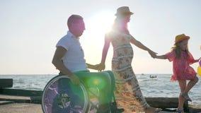 Rörelsehindrad man i rullstol med dottern och frun på blå himmel för bakgrund arkivfilmer