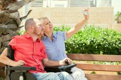 Rörelsehindrad man med hans fru som har gyckel som tar selfiefoto Royaltyfri Fotografi