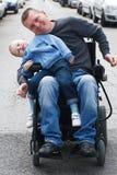 Rörelsehindrad man med sonen på rullstolen arkivfoton
