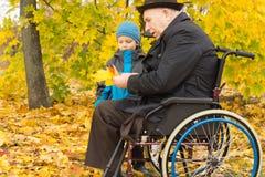 Rörelsehindrad man och hans sonson som tycker om höst arkivbilder