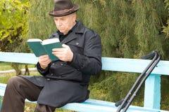 Rörelsehindrad man på kryckor som sitter att läsa Royaltyfria Bilder