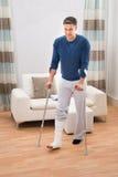 Rörelsehindrad man som använder kryckor för att gå fotografering för bildbyråer