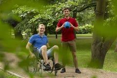 Rörelsehindrad man som spelar sporten med vännen royaltyfria bilder