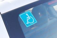 Rörelsehindrad parkeringsklistermärke på bilen Arkivbild