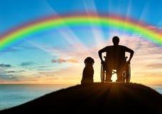 Rörelsehindrad person i en rullstol bredvid hans hund Arkivbilder
