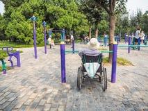 Rörelsehindrad person i en rullstol som utarbetar på offentlig utrustning royaltyfri fotografi