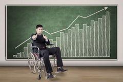 Rörelsehindrad person och finansiell graf arkivbild
