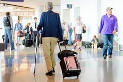 Rörelsehindrad person som går med pinnen och bagage i flygplats Arkivfoton