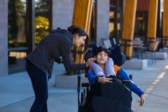Rörelsehindrad pojke i rullstol genom att använda earbuds med anhörigvårdaren Arkivfoto