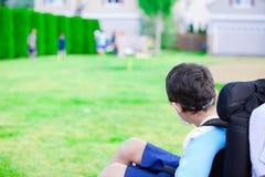 Rörelsehindrad pys i hållande ögonen på barnlek för rullstol på lek Fotografering för Bildbyråer