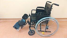Rörelsehindrad vagn Svart rullstol i sjukhuset för trans. av allvarligt dåligt folk royaltyfri bild