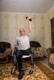 Rörelsehindrade gamala män som gör övningar med hantlar royaltyfria foton