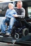 Rörelsehindrade män med sonen på rullstolelevator royaltyfria bilder