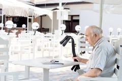 Rörelsehindrat mansammanträde på en utomhus- restaurang Arkivbild