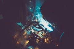 Röret för industriarbetaresvetsningrundan på en arbetstabell som producerar blått, röker, gula gnistor och reflexioner Royaltyfri Foto
