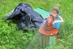 Röret och vatten för rörmokeri läcker det huvudsakliga, gammal rost för klapprörstål på gräsgolv Arkivfoto