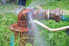 Röret och vatten för rörmokeri läcker det huvudsakliga, gammal rost för klapprörstål på gräsgolv royaltyfri fotografi