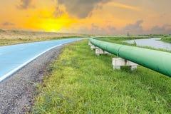 Rörledning och fördelning för rått vatten som är parallella av vägen Arkivfoton