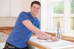Rörmokare Fixing Kitchen Tap med den justerbara skiftnyckeln Royaltyfria Bilder