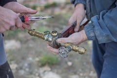 Rörmokare som arbetar genom att använda rörskiftnycklar Royaltyfri Fotografi
