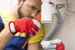 Rörmokare som fixar vaskhäverten i ett badrum royaltyfri bild
