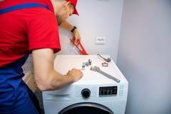 Rörmokare som installerar tvagningmaskinen royaltyfri fotografi