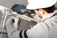 Rörmokare som reparationr några rør Arkivfoto