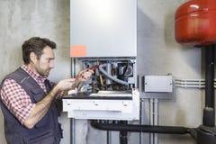Rörmokare som reparerar en kondensera kokkärl arkivfoto