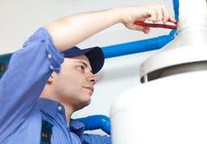 Rörmokare som reparerar en varmvattenvärmeapparat Royaltyfri Bild