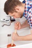 Rörmokare som unclogging en bathtubeavrinning Royaltyfri Fotografi