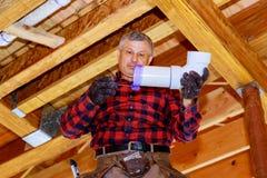 Rörmokarearbetare som installerar kloakrör i tillförselsystem i ett privat hus arkivfoto