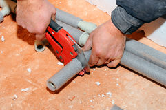 Rörmokarearbetaren med sax klipper röret bitande metall-plast- rör vid special röd sax Rörmokaren räcker arbete Royaltyfri Fotografi