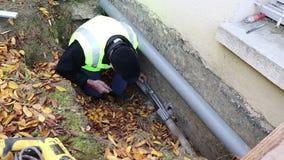 Rörmokaremannen förbereder utbytet av avrinningrören i fundamentet av huset lager videofilmer