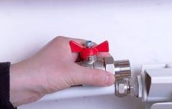 Rörmokaren håller montering i hand mot ett element fotografering för bildbyråer