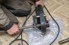 Rörmokaren pressar metallröret av pressen med fästingar royaltyfria foton