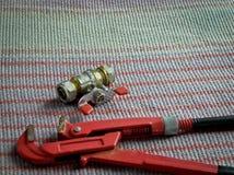 Rörmokerihjälpmedel, rörskiftnyckel och vattenkran arkivbild