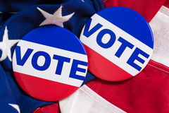 Rösta knappar på en amerikanska flagganbakgrund Arkivbilder