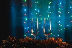 Rösten mit Champagnergläsern gegen Lichterkette und neues Jahr Stockfotografie