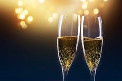 Rösten mit Champagnergläsern gegen Lichterkette und neues y Stockbilder