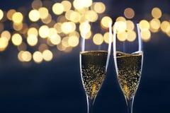 Rösten mit Champagnergläsern gegen Lichterkette und neues y Lizenzfreies Stockfoto