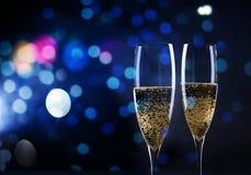 Rösten mit Champagnergläsern gegen Lichterkette und neues y Stockbild